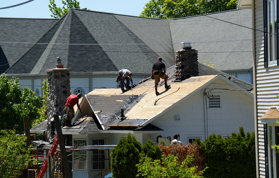 construction workers installing roof shingles in Fredericton, NB