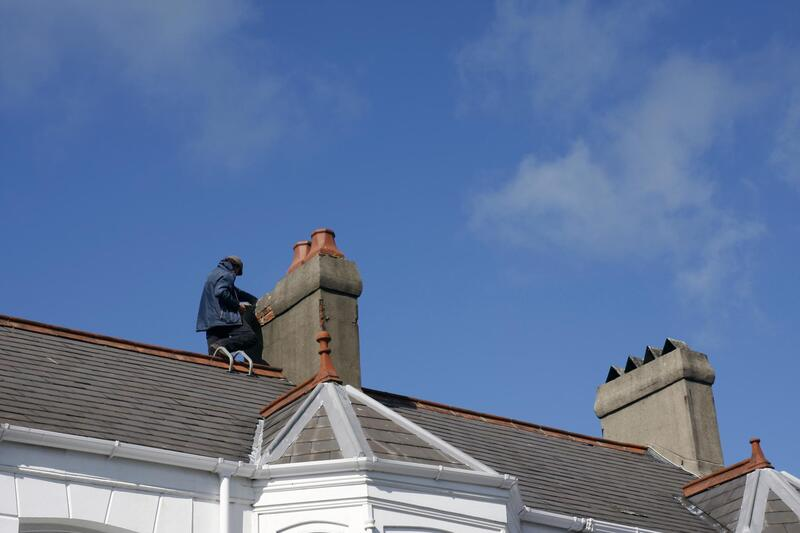 a man on the roof repairing the flashing around the chimney in Fredericton, NB