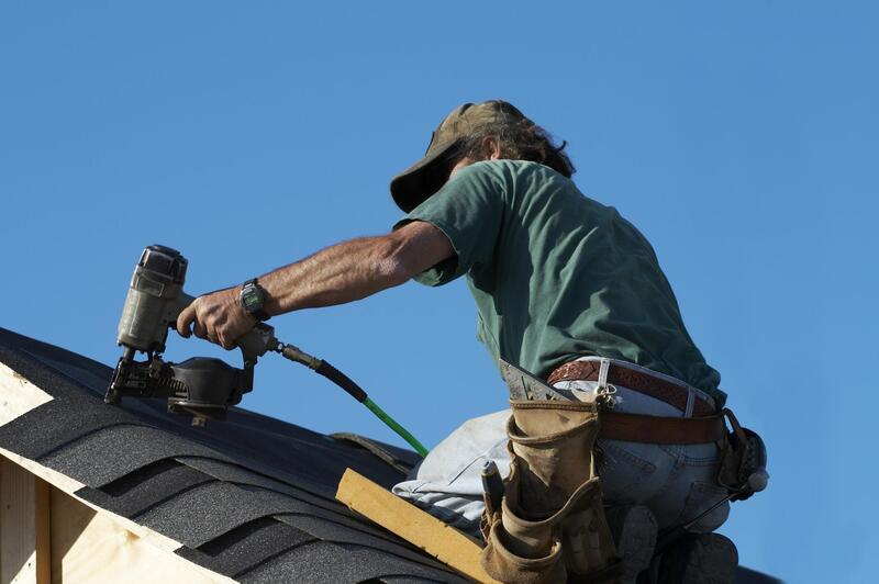 construction worker help installing roof in Fredericton, NB